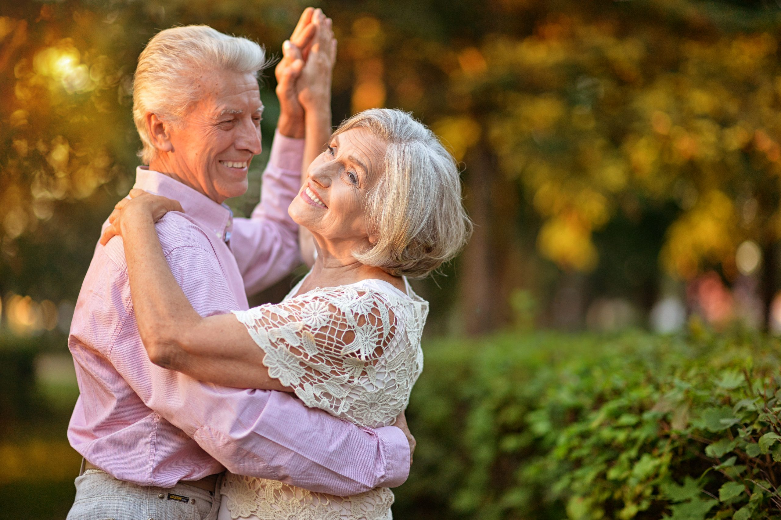 portrait of beautiful caucasian senior couple dancing in the park